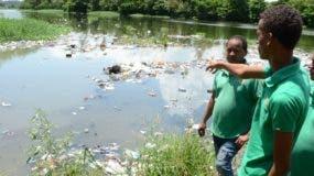 Brigadas de la Fundación Escoba muestran parte de los desechos que a diario se vierten en el río Ozama y que deben retirarlos.