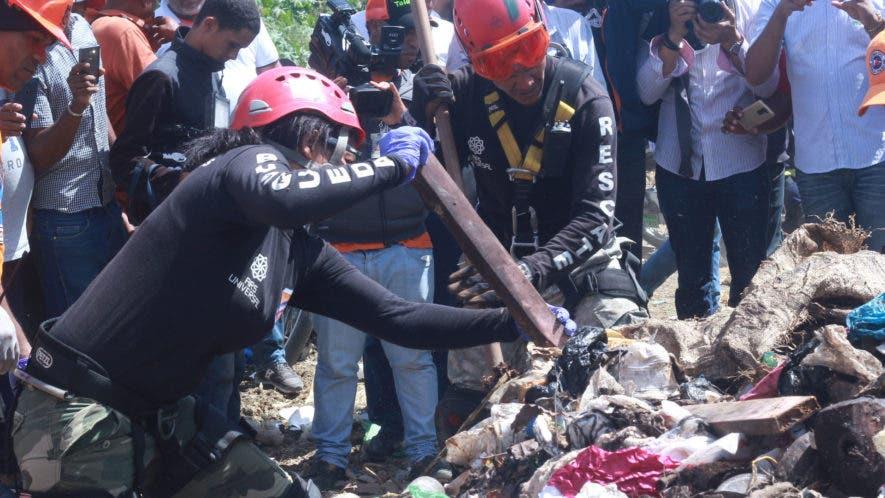 Brigadistas buscan entre los desperdicios el cadáver de Emely Peguero, luego de que el novio confesara que la mató y que la había lanzado en ese lugar. Foto: Elieser Tapia/El Día.