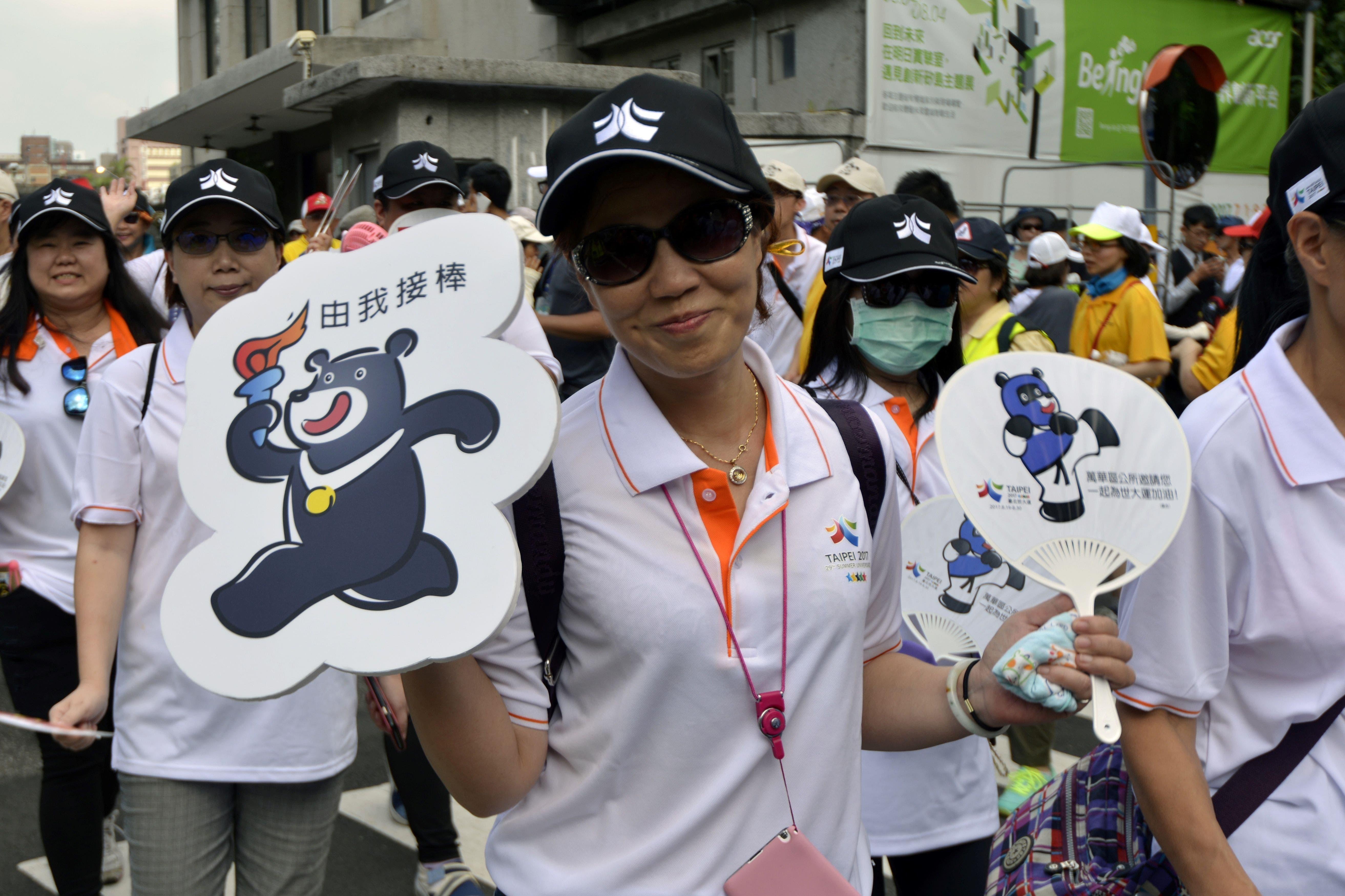 Una joven taiwanesa muestra algunos productos con la imagen de la mascota de los juegos.