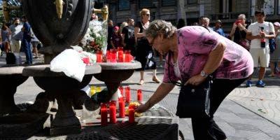 Una mujer deposita una vela en homenaje a las víctimas del atentado terrorista en La Rambla.