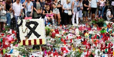 La gente está de pie junto a flores, velas y otros artículos en el bulevar de Las Ramblas, en Barcelona, al rendir homenaje a las víctimas del atentado de Barcelona, tres días después de que una furgoneta arrollara a la multitud, matando a 13 personas e hiriendo a más de 100 en agosto 20 de julio de 2017.AFP