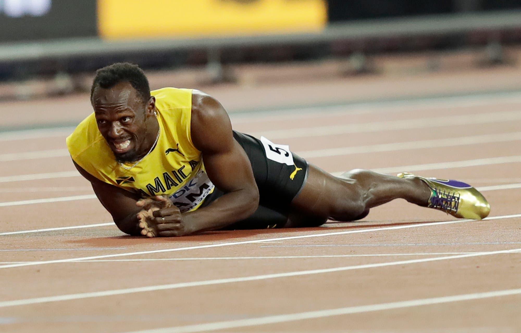 Usain Bolt tirado en la pista tras sufrir una lesión en la final del relevo 4x100 del Mundial de atletismo, en Londres, el sábado 12 de agosto de 2017. (AP Foto/Tim Ireland)