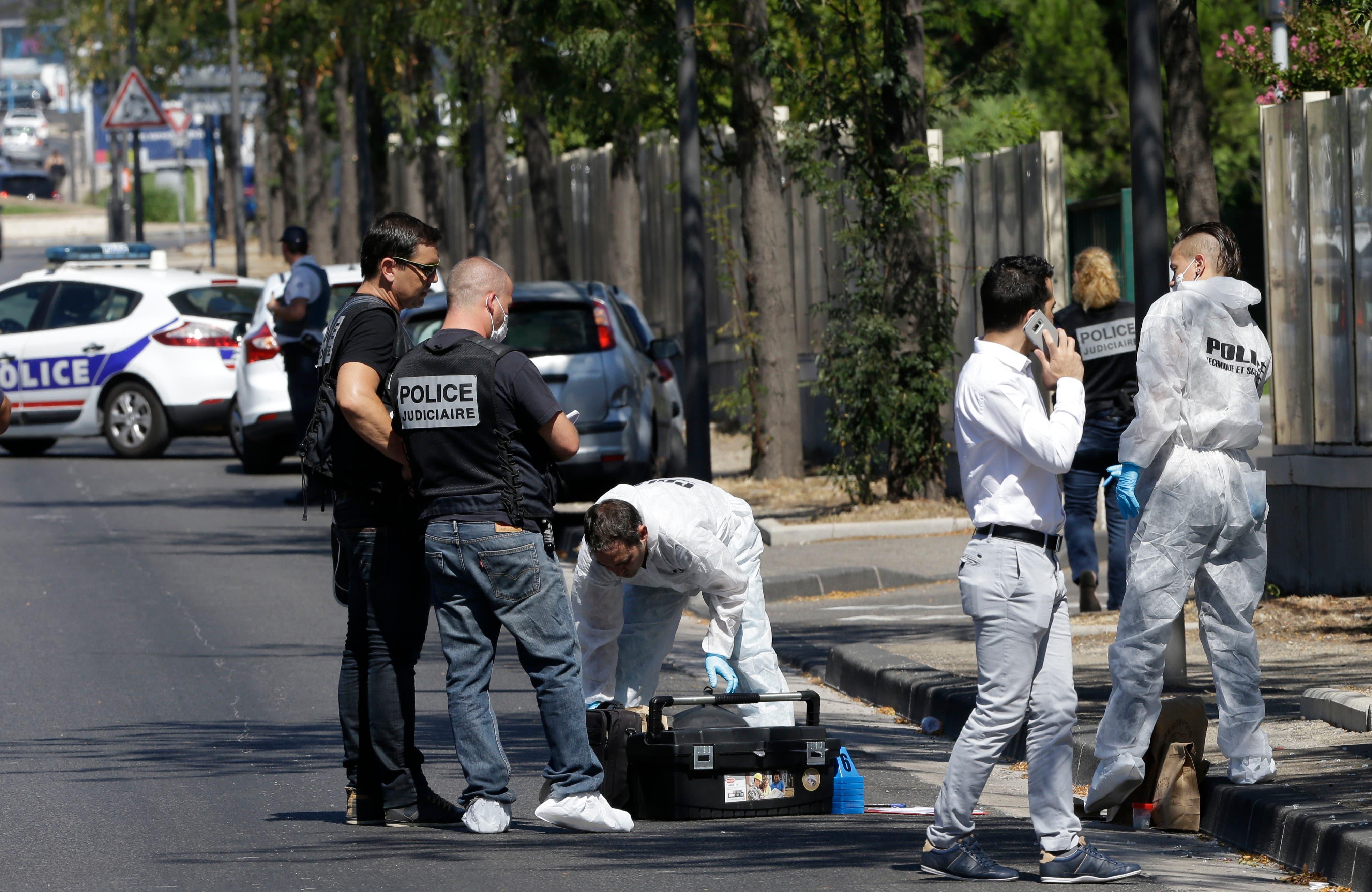 Agentes de la policía francesa trabajan cerca de un autobús en el distrito de La Valentine, después de que una camioneta embistiera contra dos paradas de autobús en la ciudad francesa de Marsella, en el sur de Francia, el lunes 21 de agosto de 2017. (AP Foto/Claude Paris)