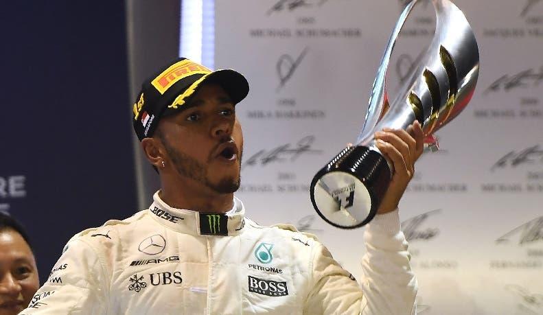 Lewis Hamilton celebra con el trofeo luego de llegar a la meta.