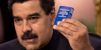 El presidente venezolano Nicolás Maduro sostiene una copia de la Constitución mientras habla en una conferencia de prensa en Caracas. Foto de archivo.