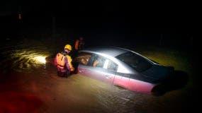 Rescatistas municipales revisan un auto abandonado en una zona inundada en Fajardo, Puerto Rico, mientras el huracán Irma cruza el norteste de la isla la noche del miércoles 6 de septiembre de 2017. (AP Foto/Carlos Giusti)