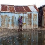 Una mujer bordea un charco mientras camina a casa en el barrio marginal de Puerto Príncipe, Haití. AP/archivo.