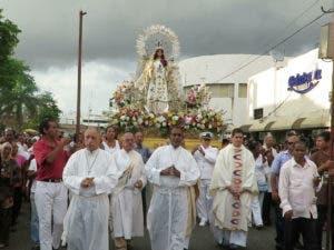 Los dominicanos acuden en procesión con la Virgen realizando cánticos y oraciones.