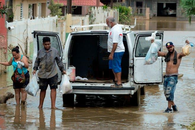 Residentes trasladando provisiones tras el paso del huracán María en Toa Baja, Puerto Rico.