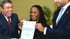Emilio Rivas y  José Dantés entregan título a una beneficiada.