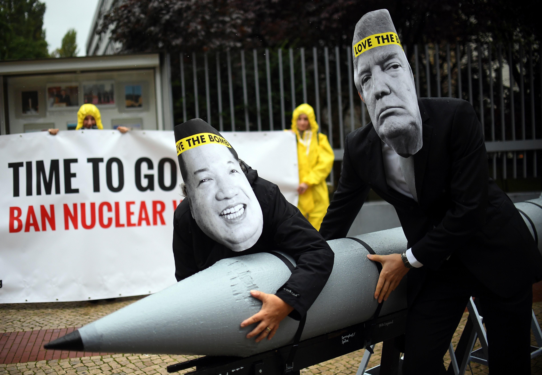 En esta imagen del 13 de septiembre de 2017, activistas de la Campaña Internacional para la Abolición de Armas Nucleares (ICAN, por sus siglas en inglés) protestan contra el conflicto entre Estados Unidos y Corea del Norte con máscaras del gobernante de Corea del Norte Kim Jong Un, a la izquierda, y del presidente de Estados Unidos, Donald Trump, ante la embajada estadounidense en Berlín, Alemania. (Britta Pedersen/dpa via AP)