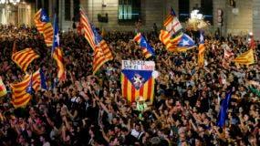 """Una bandera con el texto en catalán """"The people lead"""" se celebra cuando la gente se reúne para celebrar la proclamación de una república catalana en la plaza Sant Jaume de Barcelona el 27 de octubre de 2017."""