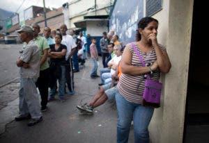 Los votantes esperan en fila para emitir sus votos fuera de una mesa de votación en Caracas. AP