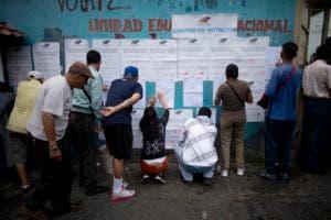 Las personas buscan sus nombres en listas de registro de votantes fuera de un colegio electoral durante las elecciones regionales en Caracas. AP