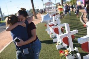 Melissa Gerber (L) y Sandra Serralde (R) se sienten cómodas al lado de 58 cruces blancas para las víctimas del tiroteo de la noche del domingo en el extremo sur de Las Vegas Strip, el 6 de octubre de 2017 en Las Vegas, Nevada.