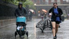 Los turistas se ejecutan para evitar la lluvia como fuertes vientos y fuertes lluvias del huracán Nate comienzan a llegar a tierra el 7 de octubre de 2017 en Nueva Orleans, Louisiana. Se espera que Nate llegue a tierra como un huracán de categoría 2 cerca de Biloxi, Mississippi más tarde esta noche. AFP