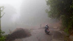 Residentes caminan bajo la lluvia cerca de un camino destrozado por un alud causado por la tormenta tropical Nate en Alajuelita, en las afueras de San José, Costa Rica, el jueves 5 de octubre de 2017. (AP Foto/Moisés Castillo).