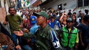Los venezolanos hacen cola afuera de una mesa de votación mientras esperan a emitir su voto durante las elecciones regionales en Caracas, Venezuela, el 15 de octubre de 2017. Los venezolanos se dirigieron a las urnas el domingo en elecciones regionales consideradas como una prueba crucial para el presidente Nicolás Maduro y la oposición después de meses de las mortales protestas callejeras no lo derrotaron/AFP