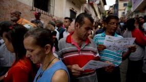 La gente lee las instrucciones de votación mientras esperan a emitir su voto para las elecciones regionales fuera de una mesa de votación en Caracas, Venezuela, el domingo 15 de octubre de 2017. AP