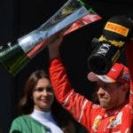 El piloto alemán Sebastian Vettel levanta la copa de ganador.