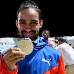 Luguelín Santos muestra con orgullo la medalla de oro.
