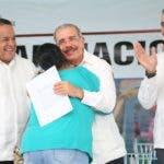 Emilio Toribio Olivo, el presidente Danilo Medina y José Dantés felicitan a una de las parceleras.