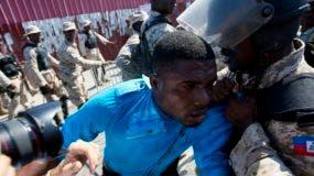 Un manifestante es agarrado y empujado por un oficial de policía durante una marcha de protesta en respuesta a los hallazgos de una investigación del Senado sobre el fondo PetroCaribe, en Puerto Príncipe, Haití, el martes 5 de diciembre de 2017. AP