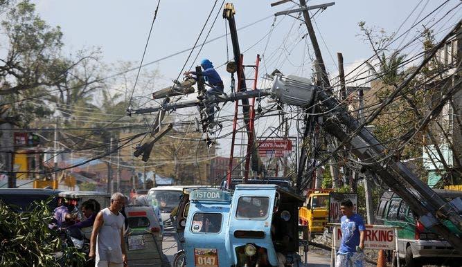 Trabajadores reparando un poste de luz en Filipinas tras el paso de un tifón EFE