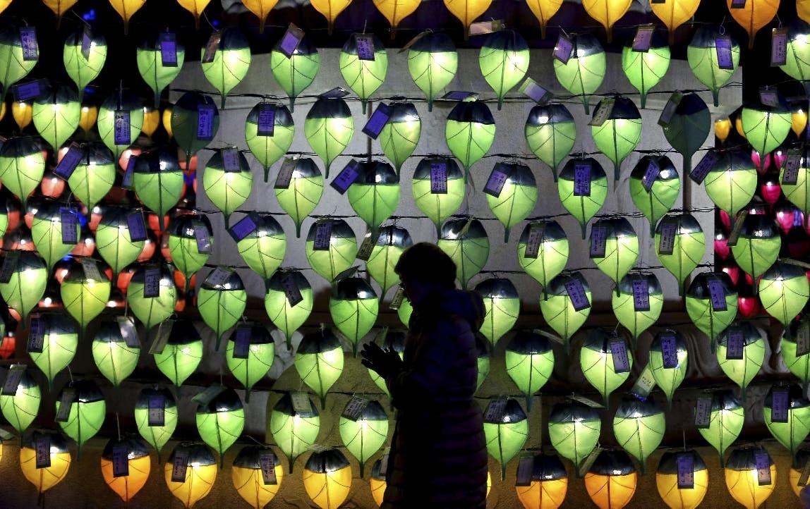 Una mujer ora frente a filas de linternas para celebrar el Año Nuevo en el templo budista de Jogyesa en Seúl, Corea del Sur.. (AP Foto/Ahn Young-joon)
