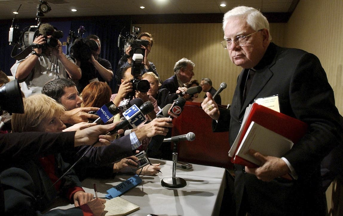 Esta foto del martes 12 de noviembre del 2002 muestra al cardenal Bernard Law, derecha, saliendo de una conferencia de prensa durante la reunión anual de la Conferencia Estadounidense de Obispos Católicos, en Washington. (AP Foto/Ken Lambert, Archivo)