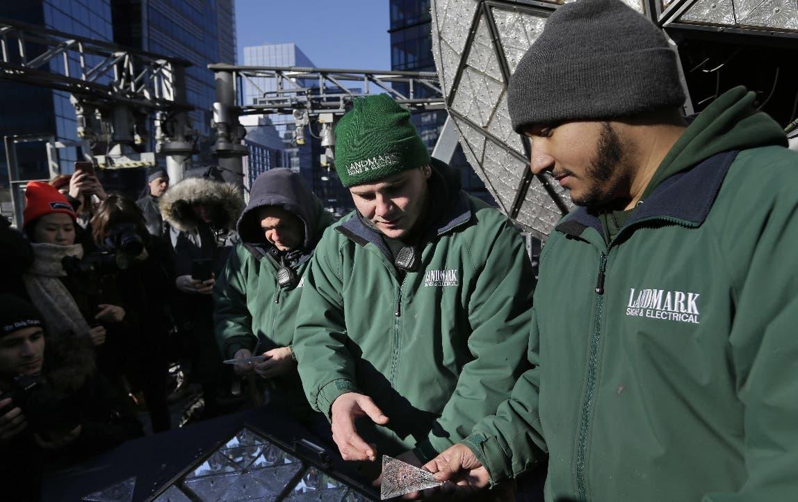 Los trabajadores se preparan para instalar los últimos paneles en la bola de Nochevieja sobre Times Square, Nueva York. AP