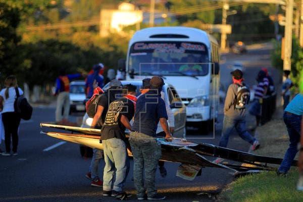 Un grupo de manifestantes destruye una valla en Tegucigalpa
