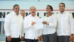 El presidente Danilo Medina entrega un título definitivos a una de las beneficiadas.