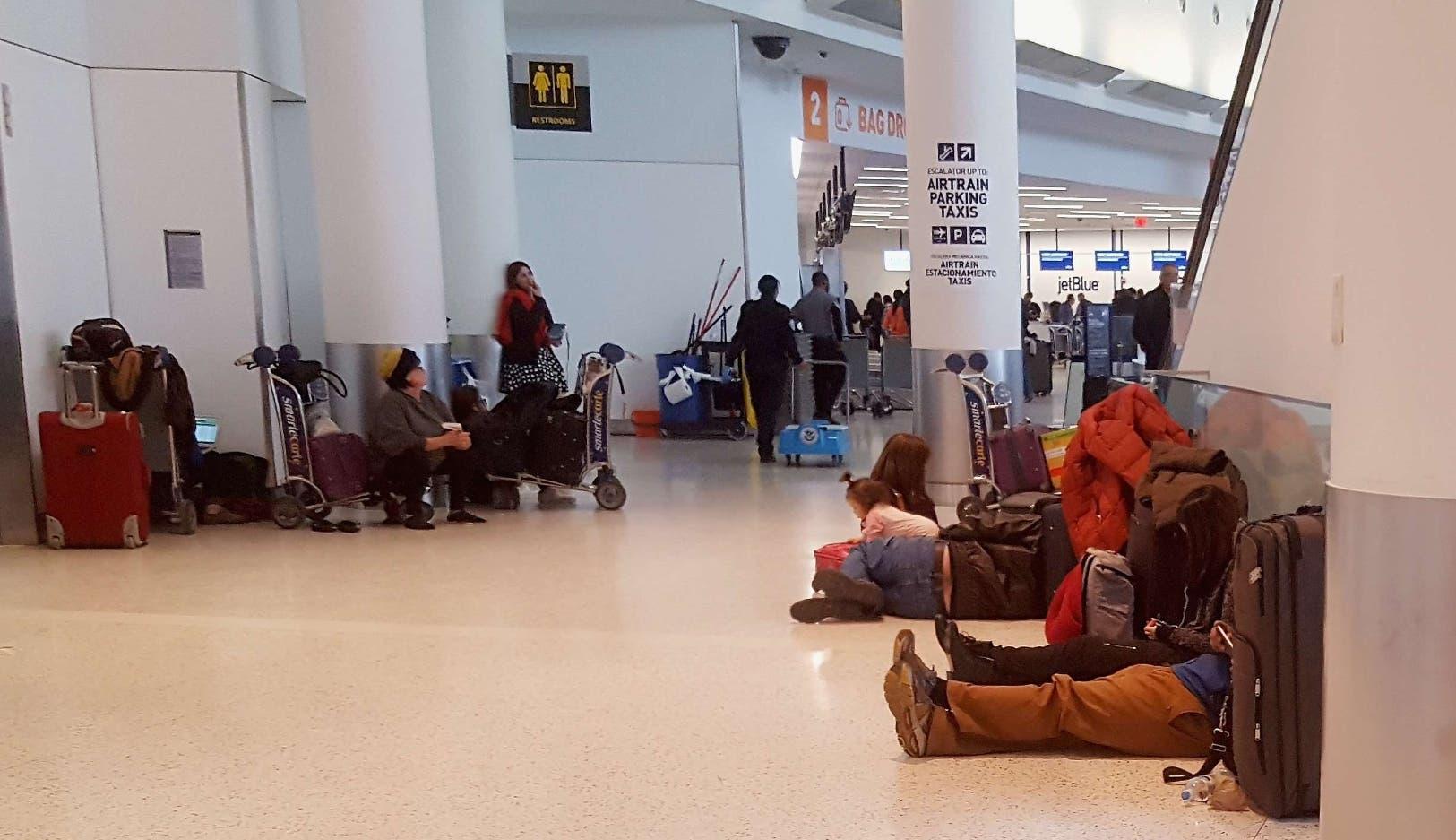 En el aeropuerto de JFK  se puede  ver a numerosos viajeros durmiendo o esperando una oportunidad para viajar a su destino final.