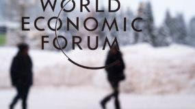 Dos personas caminan por detrás del logo del Foro Económico Mundial en el centro de conferencias donde se celebra la cumbre, en Davos, Suiza, el 21 de enero de 2018. (AP Foto/Markus Schreiber)