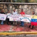Venezolanos residentes en el país que acudieron hoy frente a la Cancillería previo al diálogo entre el Gobierno y la oposición de su país.