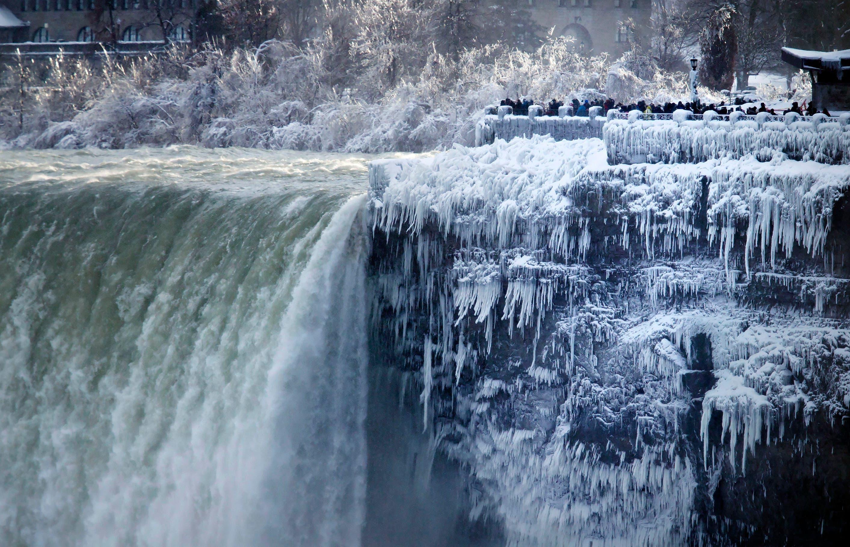 Visitantes toman fotografías en la catarata Horseshoe, en las Cataratas del Niágara, Ontario, el 2 de enero de 2018. (Aaron Lynett/The Canadian Press via AP)
