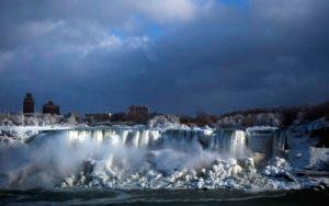 El agua corre por la catarata Estadounidense entre el hielo, en el lado canadiense de las Cataratas del Niágara, en Ontario, el 2 de enero de 2018.  (Aaron Lynett/The Canadian Press via AP)