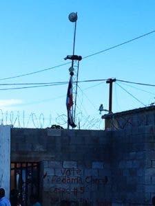 Una bandera dominicana, rota, colgada en una antena en la frontera con Haití.