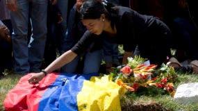 Yandribell Diaz, hija de José Díaz Pimentel, coloca una bandera sobre la tumba de su padre en un cementerio de Caracas, Venezuela, el sábado 20 de enero de 2018. Díaz Pimentel era parte del grupo rebelde liderado por el expolicía venezolano Oscar Pérez, que fallecieron a inicios de semana en una operación de las fuerzas de seguridad. (AP Foto/Fernando Llano)