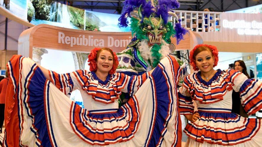 Mujeres que visten atuendos tradicionales posan en el stand de República Dominicana durante la Feria Internacional de Turismo (FITUR) en Madrid/ AFP