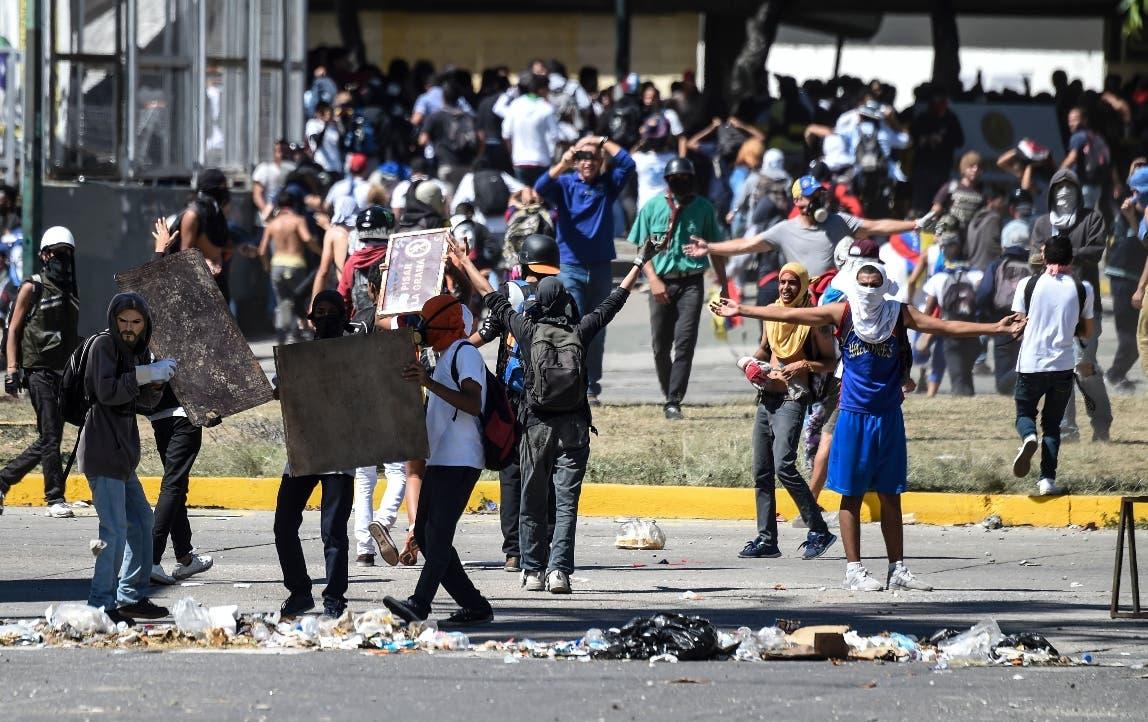 Jóvenes encapuchados respondieron con piedras a la Policía. AFP