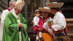 Una familia camina hacia el altar ante el papa Francisco, en una misa por el Día de los Migrantes y los Refugiados, en la Basílica de San Pedro del Vaticano, el domingo 14 de enero de 2018. (AP Foto/Alessandra Tarantino)