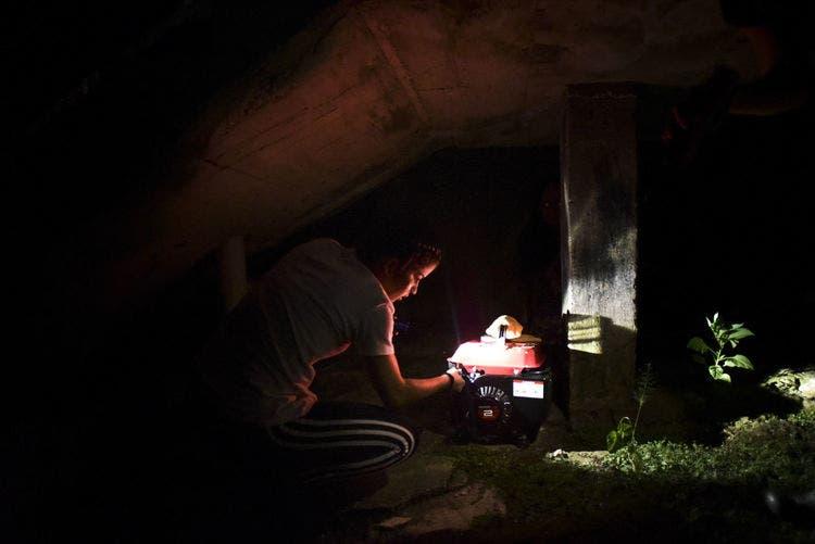 En esta foto de archivo, 21 de diciembre de 2017, Karina Santiago González enciende un pequeño generador en Morovis, Puerto Rico. Una junta federal de control solicitó un préstamo de 300 millones de dólares para la empresa de electricidad de Puerto Rico el viernes 16 de febrero de 2018 después que un juez federal bloqueó un préstamo de 1.000 millones a pesar de las advertencias de que el territorio debería racionar el suministro. AP