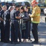 Erik Scott, del Departamento de Bomberos de Los Ángeles, a la derecha, agentes de policía y funcionarios escolares se reúnen afuera de Belmont High School   (AP Photo / Damian Dovarganes)