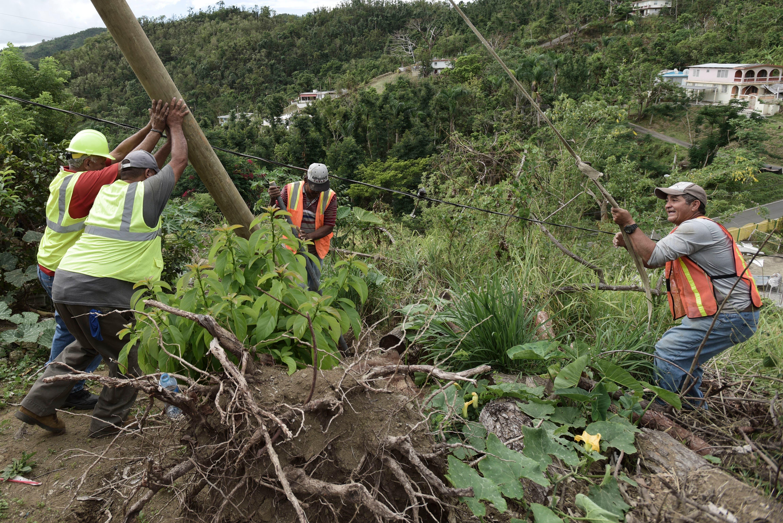 En esta imagen del 31 de enero de 2018, el subdirector de obra pública Ramón Méndez, de casco, a la izquierda, participa con trabajadores municipales en la colocación de un poste para restaurar el suministro eléctrico a una vivienda próxima, cuatro meses después del paso del huracán María por el sector de El Ortiz en Coamo, Puerto Rico. Una explosión e incendio en una subestación de luz dejó el domingo 11 de febrero a oscuras gran parte del norte de Puerto Rico, en un revés a los esfuerzos de la isla para restaurar la energía más de cinco meses después del paso del huracán. (AP Foto/Carlos Giusti)