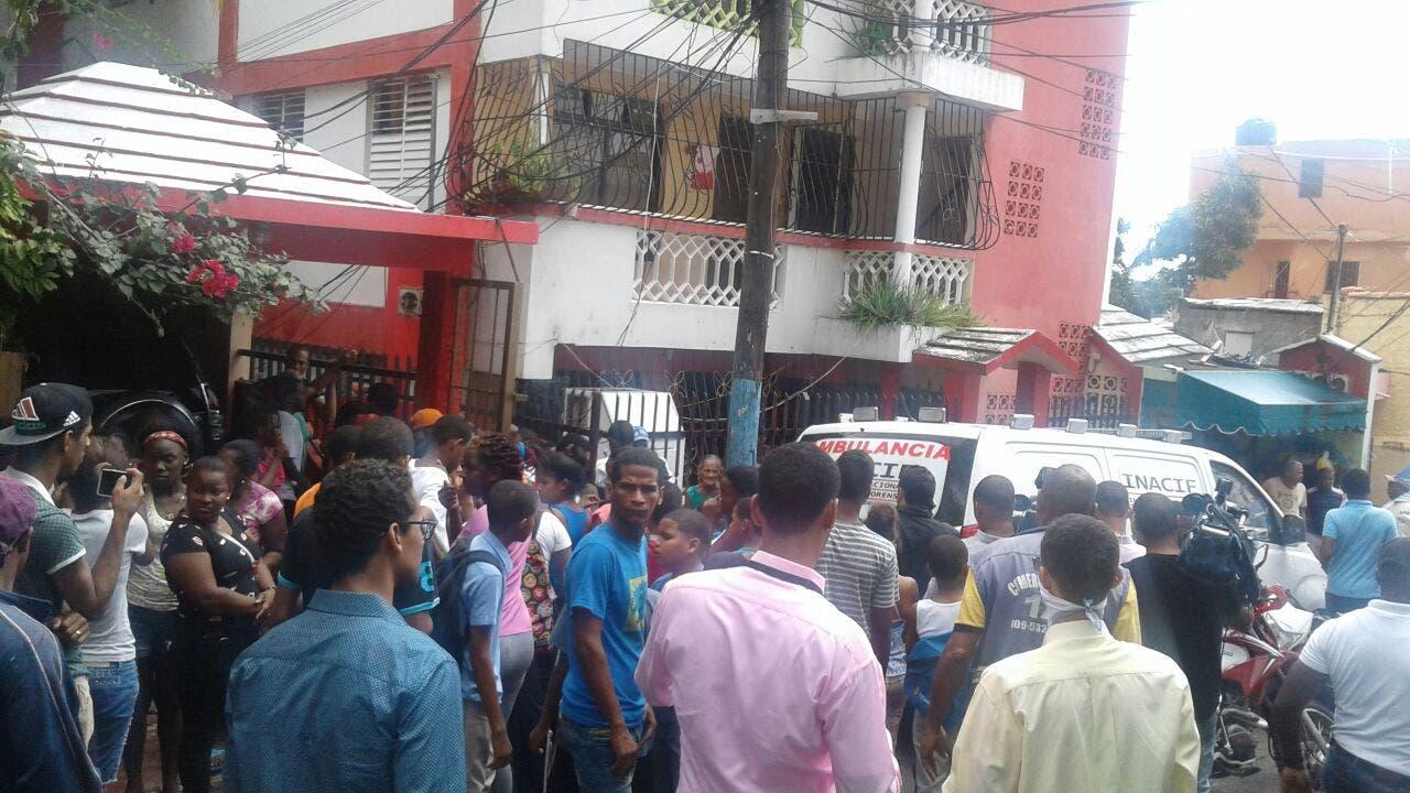 Moradores se acercan a la residencia donde fueron encontrados los cadáveres.
