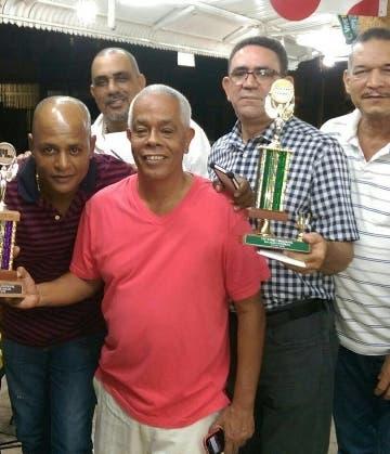 El equipo de dominó Los Canucos con sus trofeos .
