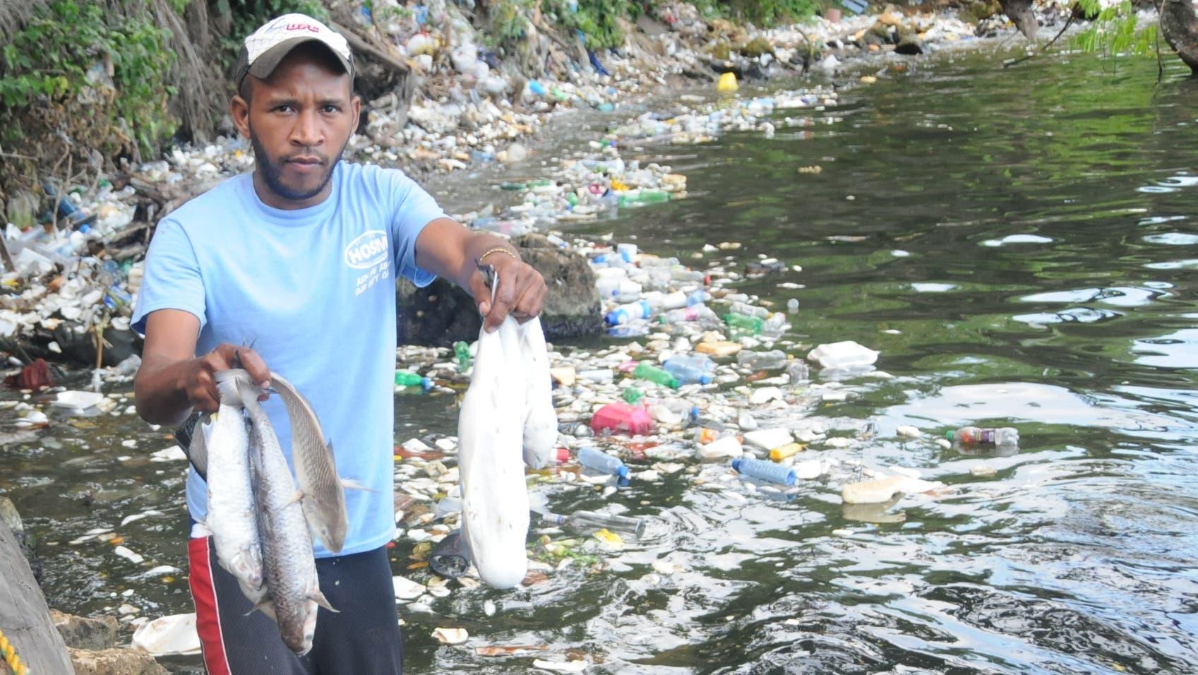 Teiddy  de León muestra parte de los peces  muertos por contaminación de las aguas, que lucen turbias por demás . NICOLÁS MONEGRO