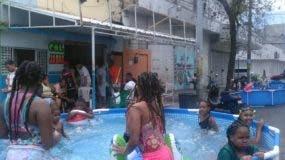 Niños disfrutando en una piscina instalada en una calla de Villa Juana.